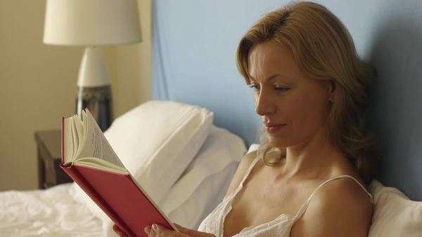 Woman reading in bedroom. Royalty-free stock video