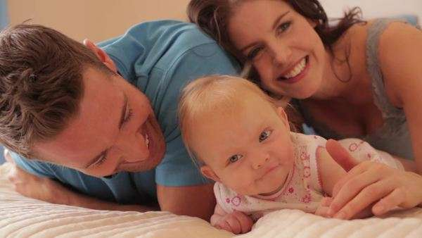 Young family with baby on bed indoors. Royalty-free stock video