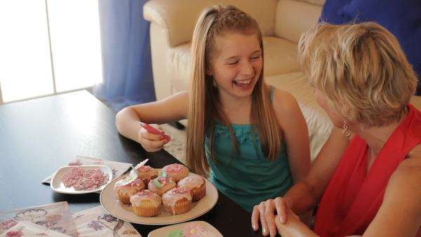 Dolly shot of grandmother and granddaughter making cup cakes together indoors. Royalty-free stock video