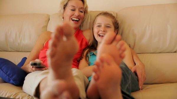 Dolly shot of grandmother and granddaughter watching TV together indoors. Royalty-free stock video