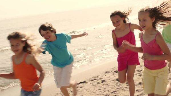 Five children running towards camera on beach. Royalty-free stock video