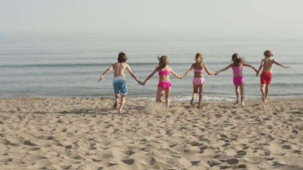 Five children running away from camera down beach to the sea. Royalty-free stock video