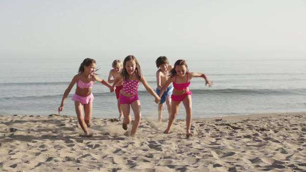 Slow motion of five children running towards camera on beach. Royalty-free stock video