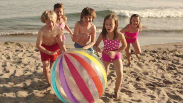 Slow motion of five children running towards camera pushing beach ball on beach. Royalty-free stock video