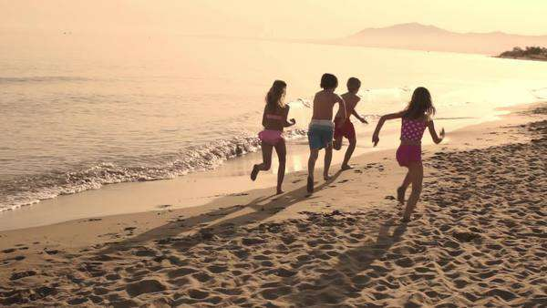 Five children running away from camera on beach. Royalty-free stock video
