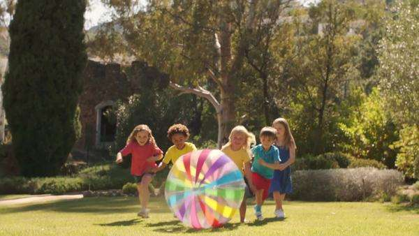 Slow motion of five children pushing beach ball towards camera in park. Royalty-free stock video