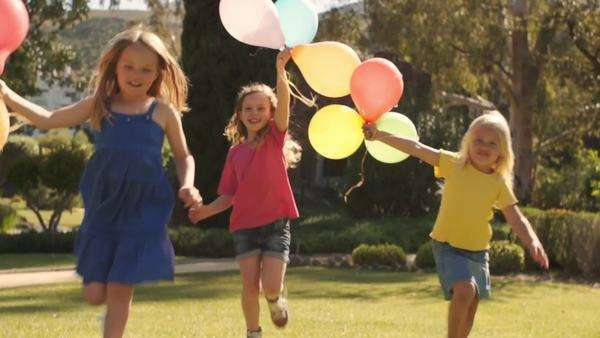 Lift up of three girls running towards camera with balloons. Royalty-free stock video