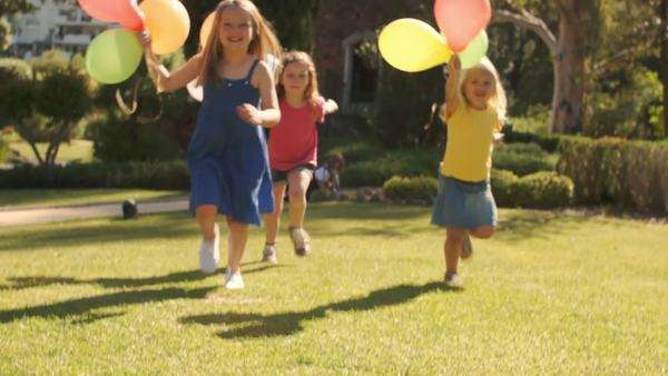 Lift up slow motion of three girls running towards camera with balloons. Royalty-free stock video