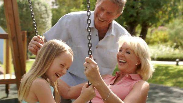 Slow motion of grandfather pushing grandmother and granddaughter on swing in park. Royalty-free stock video