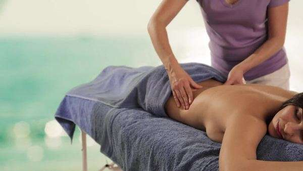 dolly shot of young woman having massage, sea background Royalty-free stock video