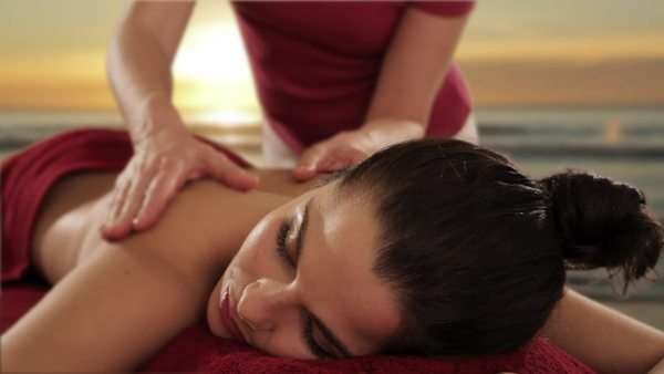 dolly shot of young woman having massage, sunset and beach background Royalty-free stock video
