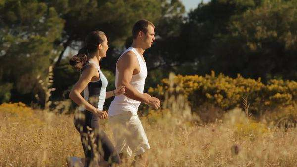 pan shot of young couple running in the countryside Royalty-free stock video