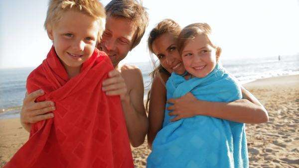 mother and father cuddling children on towels on beach Royalty-free stock video