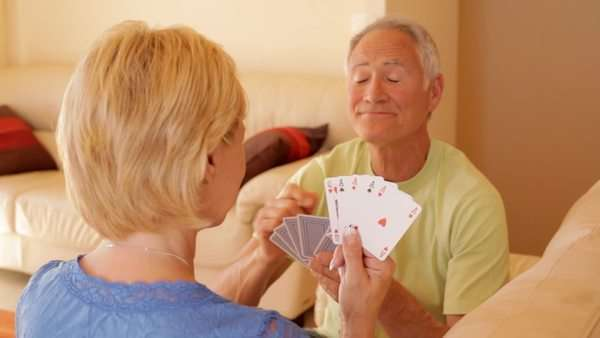 dolly shot of senior couple relaxing on sofa playing cards Royalty-free stock video