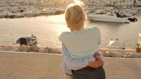 senior couple hugging and twirling by marina in sunset Royalty-free stock video