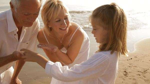 grandparents and granddaughter on beach with shells Royalty-free stock video