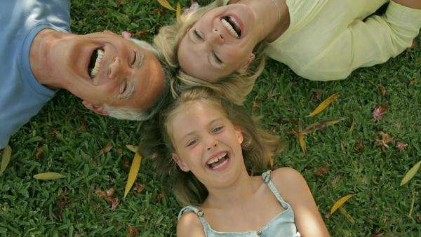 head and shoulders of grandparents and granddaughter lying on grass laughing Royalty-free stock video