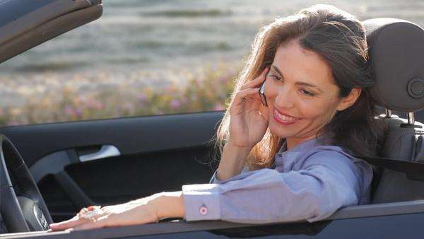 Woman in convertible car talking on cell phone. Royalty-free stock video
