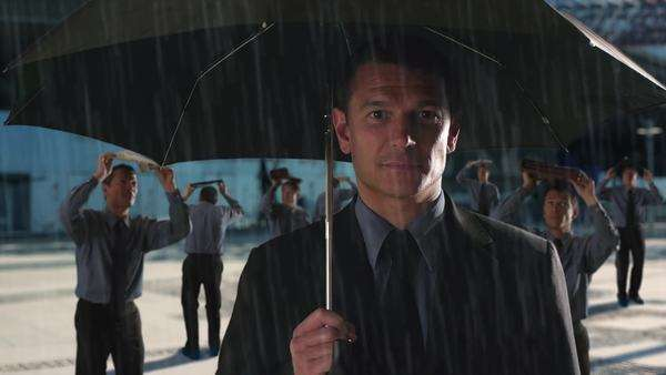 Businessman standing under umbrella in the rain. Royalty-free stock video