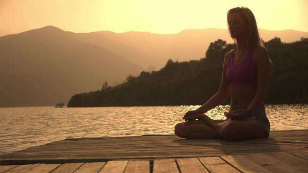 Low angle dolly shot of woman meditating on dock. Royalty-free stock video