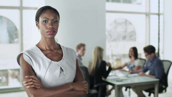 An african-american business woman stands in the foreground as a group of people sit at a table in the background Royalty-free stock video
