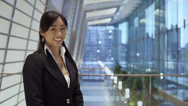 An asian business woman smiles at the camera in a brightly lit atrium lobby Royalty-free stock video