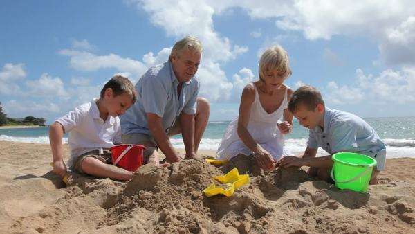 Grandparents play with grandchildren at beach Royalty-free stock video