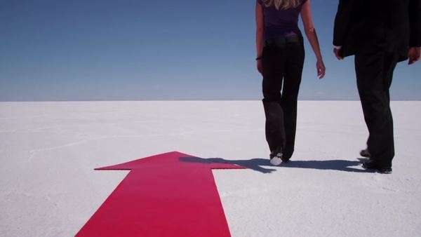 Businesspeople walk by red arrow at salt flat Royalty-free stock video