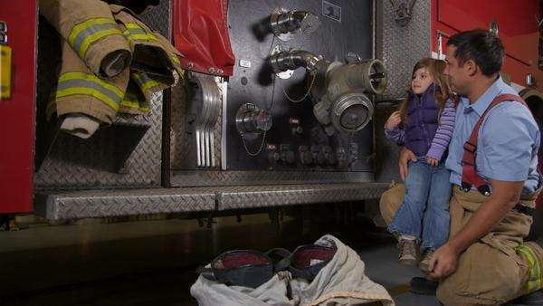 Firefighter showing young girl fire truck Royalty-free stock video