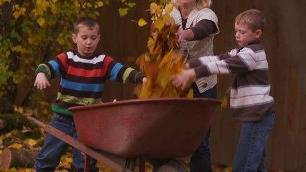 Kids and Mom pick up autumn leaves Royalty-free stock video