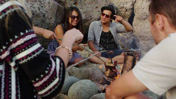 Group of young people hanging out at beach around campfire Royalty-free stock video
