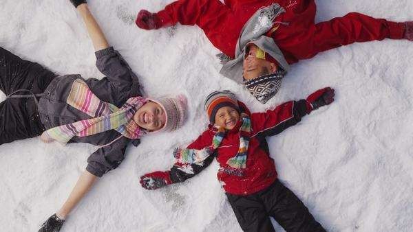 Family laying in winter snow, overhead shot Royalty-free stock video
