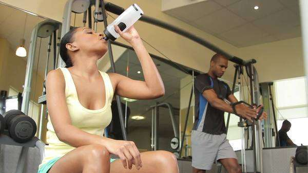 Female drinking water and male working out in gym Royalty-free stock video