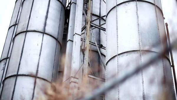 Large storage cylinders tower behind an overgrown fence with barbed-wire Royalty-free stock video