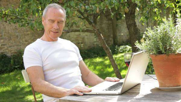 Senior male sitting at table in garden working on laptop Royalty-free stock video