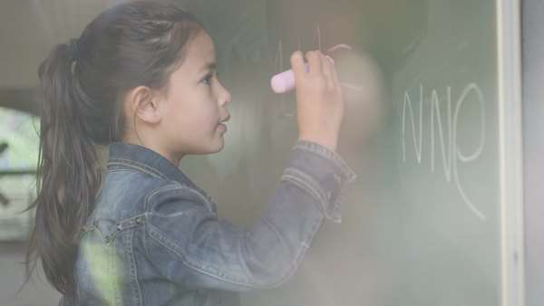 Girl writing on blackboard in classroom / Breda, Noord-Brabant, Netherlands Royalty-free stock video