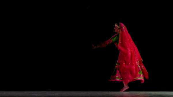 Indian woman in traditional dance costume finish her routine against a black background  Full length shot with dancer at one side Royalty-free stock video
