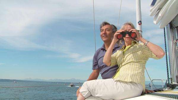 Mature couple looking through binoculars while sitting on the deck of a boat, sailing on the Puget Sound in Seattle, Washington Royalty-free stock video