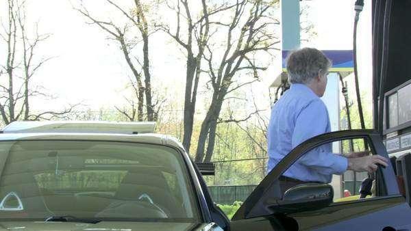 Medium long shot of a man getting out of his car and starting to fill his car with premium gas  Camera moves on jib arm throughout Royalty-free stock video