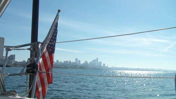 Stars and Stripes in foreground on a yacht sailing on the Puget Sound in Seattle, Washington with Seattle city skyline in background Royalty-free stock video