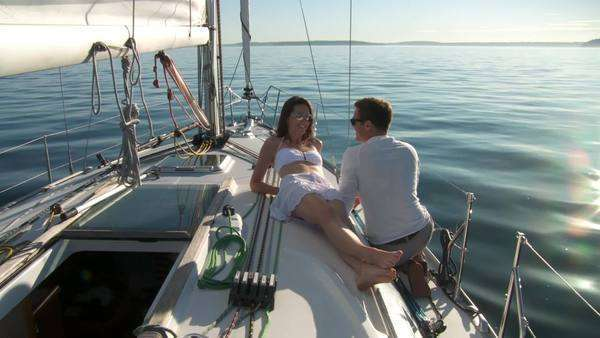 Young couple relax on the deck of a sail boat, with sunshine and sparkling water on the Puget Sound in Seattle, Washington  Wide shot Royalty-free stock video
