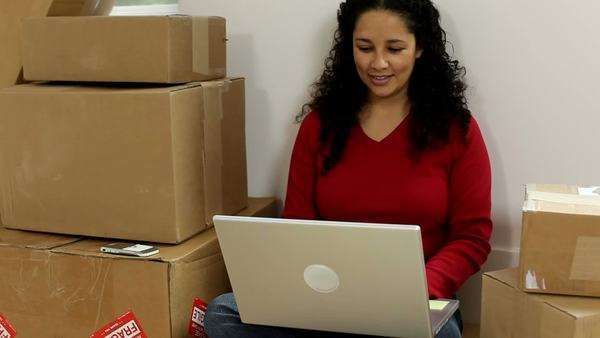 Woman sitting by unpacked boxes with laptop Royalty-free stock video