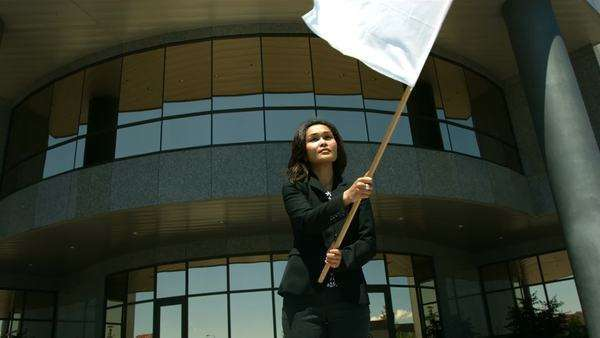 Businesswoman in front of office building waving white flag Royalty-free stock video
