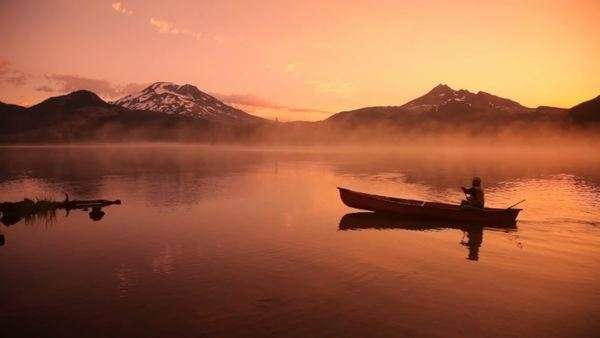 Man paddles canoe across lake at sunrise Royalty-free stock video