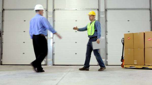 Businessman meets with employee in shipping warehouse Royalty-free stock video