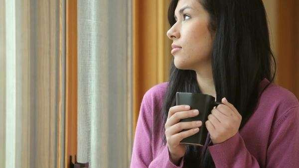 Depressed woman looking out window, holding mug of coffee Royalty-free stock video