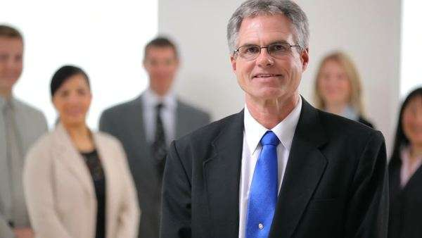 Portrait of mature business man with co-workers in background Royalty-free stock video