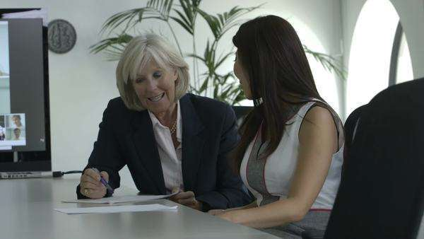 Two women talk and look over some paperwork in a boardroom Royalty-free stock video