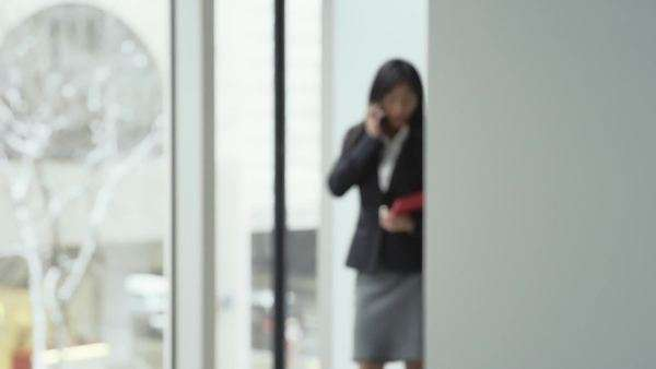 An asian business woman talks on her phone happily  by a window in a large office building Royalty-free stock video