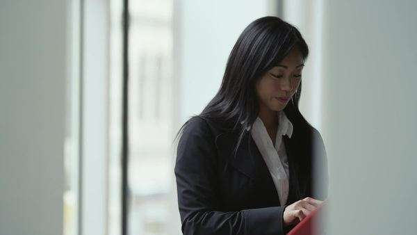 An asian business woman is working on an ipad then walks toward a window in an office building Royalty-free stock video